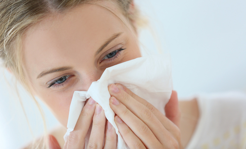 cold and flu - young woman with cold blowing her runny nose