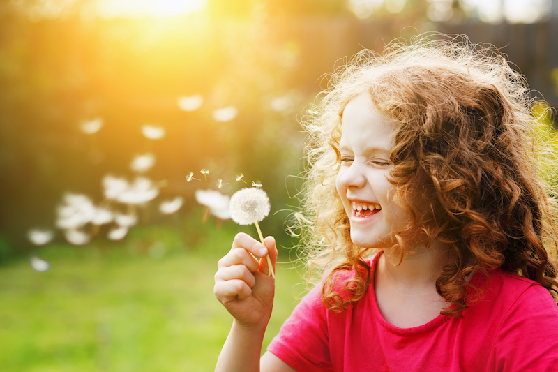 allergies - little girl blowing dandelion