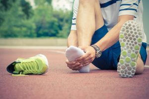 sprains and strains - jogger sitting on track holding injured foot