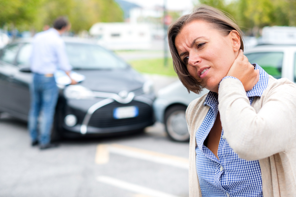 woman holding neck after being injured in a car accident