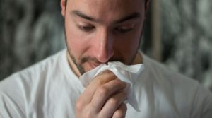 man with seasonal allergies holding tissue to nose