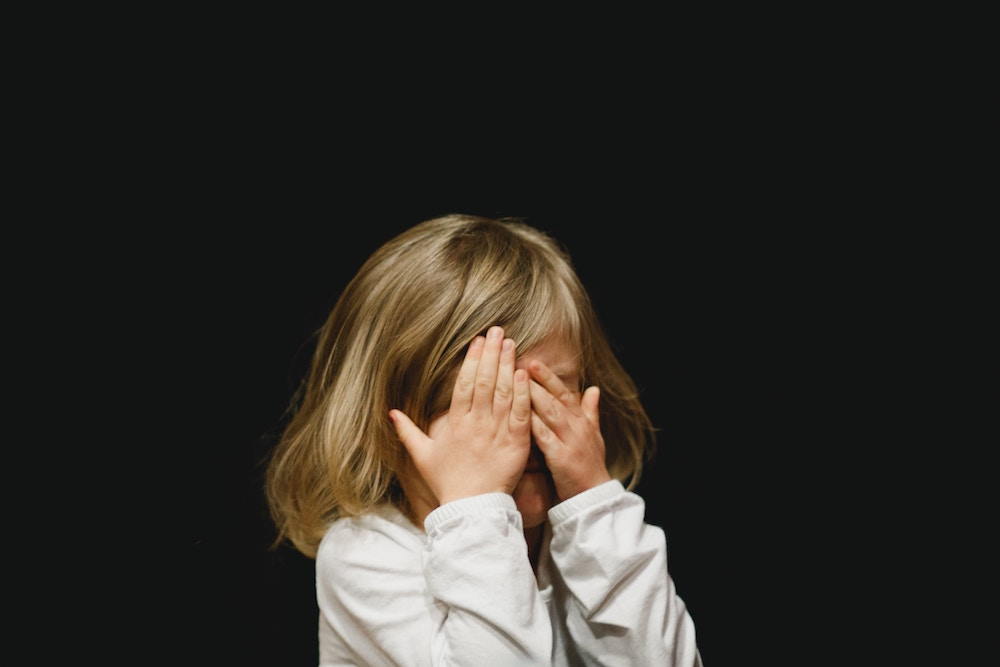 girl with hands covering face due to Conjunctivitis