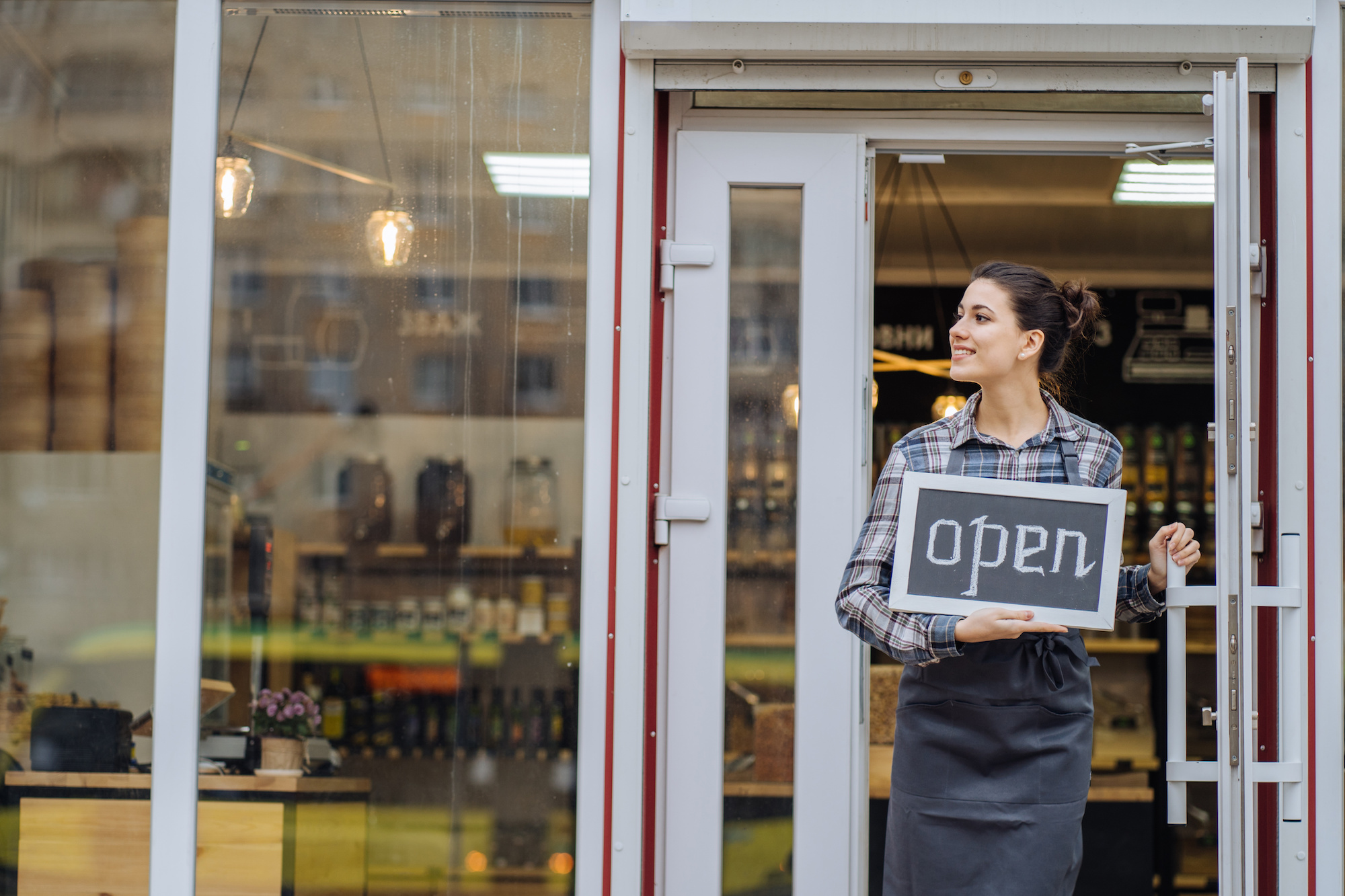 woman holding open sign in shop front uses Liberty Urgent Care Covid-19 Return to Work services